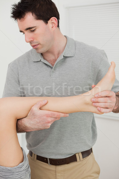 Physio folding the leg of a patient in a physio room Stock photo © wavebreak_media