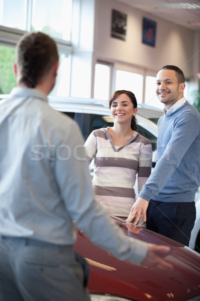 Couple smiling and chatting with a salesman in a carshop Stock photo © wavebreak_media