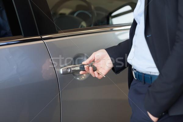 Man opening a car door with a key in a car dealership Stock photo © wavebreak_media