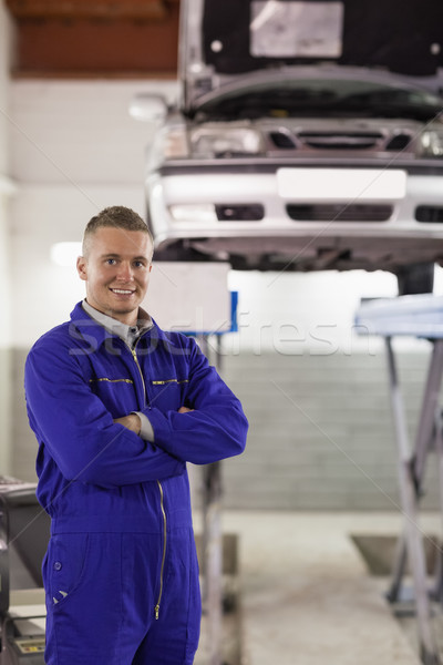Smiling mechanic looking at camera next to a car in a garage Stock photo © wavebreak_media