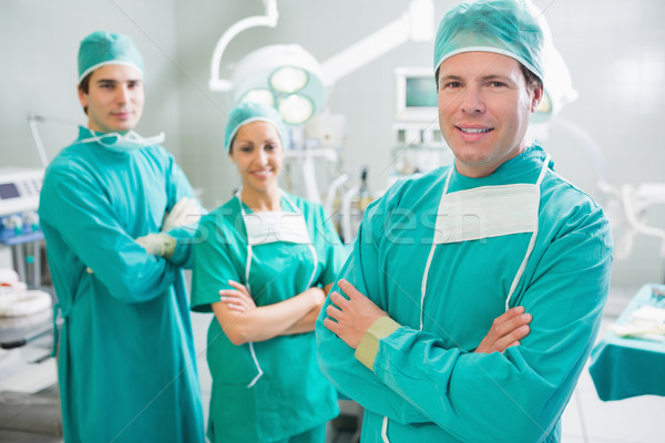 Surgical team smiling with arms crossed in an operating theatre Stock photo © wavebreak_media