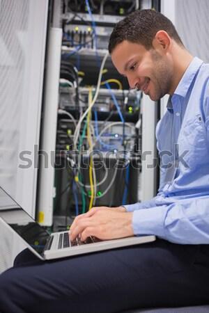 Man using laptop beside servers in data center Stock photo © wavebreak_media
