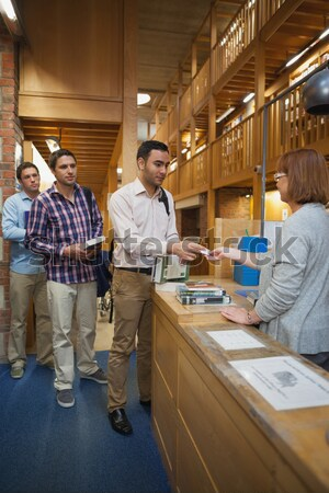Librarian scanning book and handing to woman at library desk Stock photo © wavebreak_media