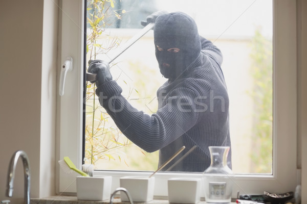 Burglar breaking a kitchen window with a crobar from outside Stock photo © wavebreak_media