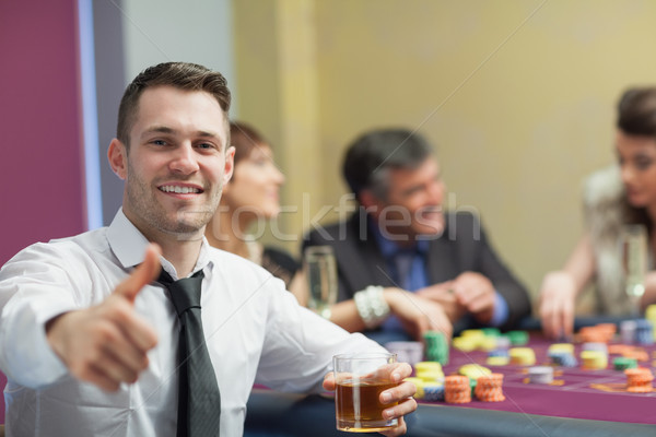 Man giving thumbs up and holding whiskey glass at roulette table Stock photo © wavebreak_media