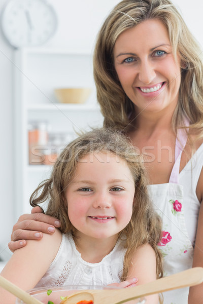 Smiling mother hugging daughter while looking directly into the camera and making salad Stock photo © wavebreak_media