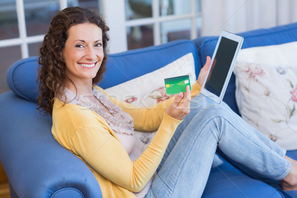 Pretty brunette relaxing on the couch with tablet Stock photo © wavebreak_media