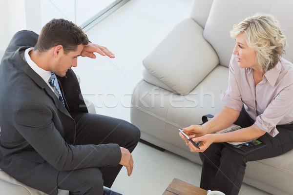 Businessman and his secretary sitting on sofa at home Stock photo © wavebreak_media