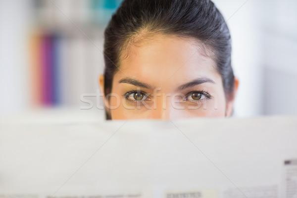 Businesswoman peeking over newspaper Stock photo © wavebreak_media