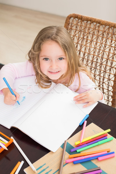 Smiling little girl colouring at the table Stock photo © wavebreak_media