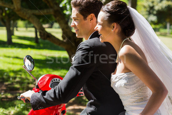 Stock photo: Newlywed couple sitting on scooter in park