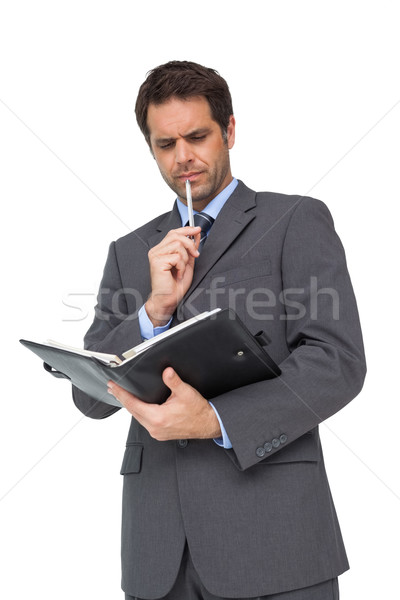 Handsome thoughtful businessman holding his diary Stock photo © wavebreak_media