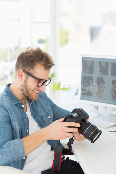 Handsome photographer holding his camera and smiling Stock photo © wavebreak_media