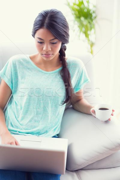 Pretty girl sitting on a sofa using laptop Stock photo © wavebreak_media