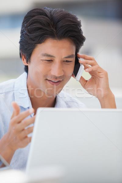 Feliz homem usando laptop falante telefone fora Foto stock © wavebreak_media