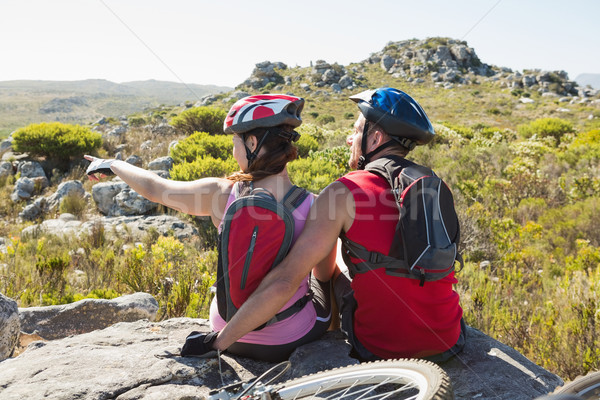Fit cyclist couple sitting at the summit looking around Stock photo © wavebreak_media