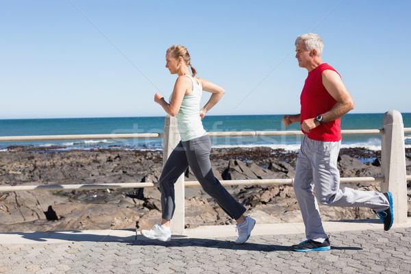 Fit mature couple jogging together on the pier Stock photo © wavebreak_media