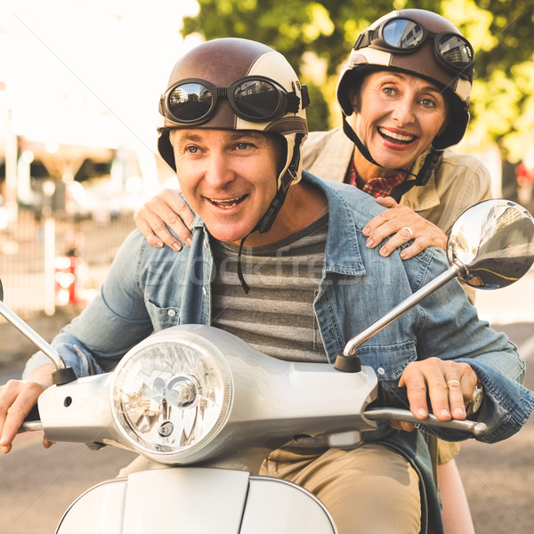 Stock photo: Happy mature couple riding a scooter in the city