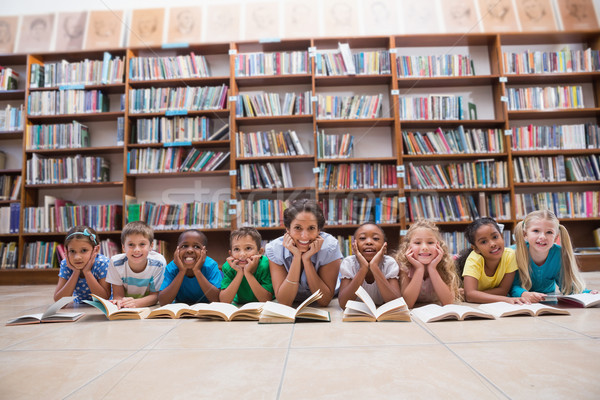 Cute pupils and teacher lying on floor in library Stock photo © wavebreak_media