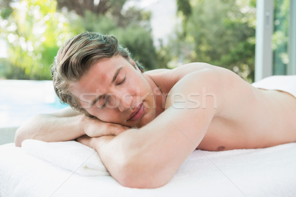 Handsome man lying on massage table at spa center Stock photo © wavebreak_media