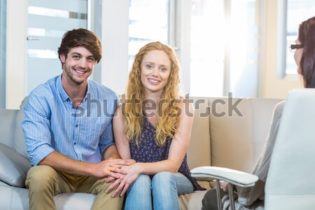 Smiling colleagues sitting on couch looking at camera Stock photo © wavebreak_media