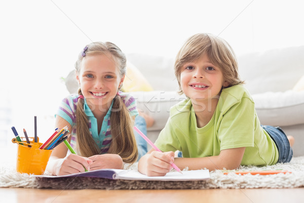 Portrait of happy siblings drawing while lying on rug Stock photo © wavebreak_media