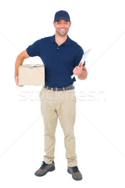 Delivery man with package and clipboard on white background Stock photo © wavebreak_media