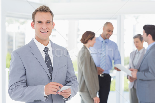 Businessman texting while his colleagues discussing Stock photo © wavebreak_media