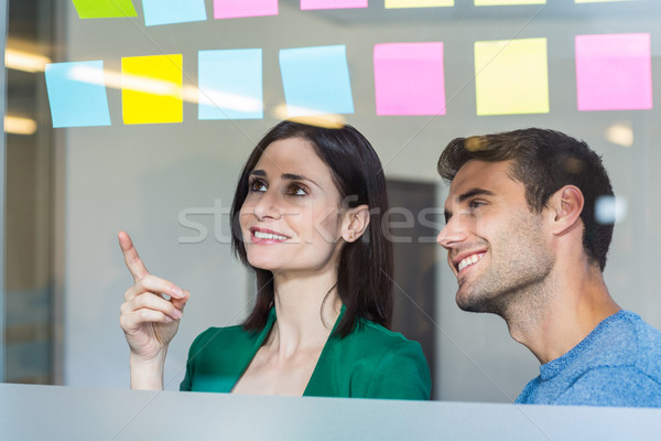 Sorridente parceria olhando notas escritório mulher Foto stock © wavebreak_media