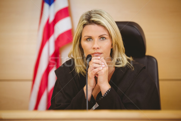 Stock photo: Portrait of a serious judge with american flag behind her