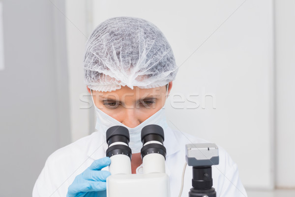 Scientist working attentively with microscope Stock photo © wavebreak_media