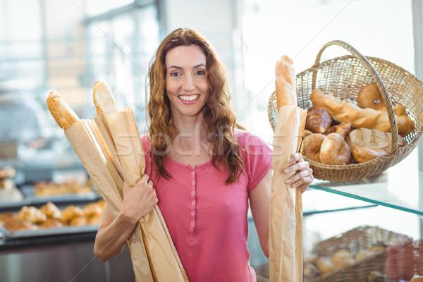 Pretty brunette holding baguettes Stock photo © wavebreak_media
