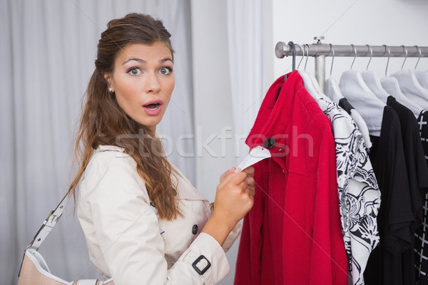 Portrait of surprised woman holding  price tag and looking at ca Stock photo © wavebreak_media