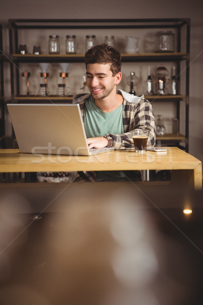 Smiling hipster sitting and using laptop Stock photo © wavebreak_media