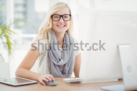 Woman at computer against blue bars in blurry office Stock photo © wavebreak_media