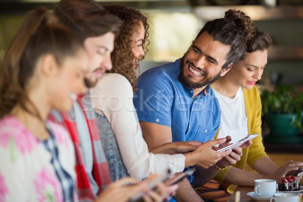 Cheerful friends using mobile phone Stock photo © wavebreak_media