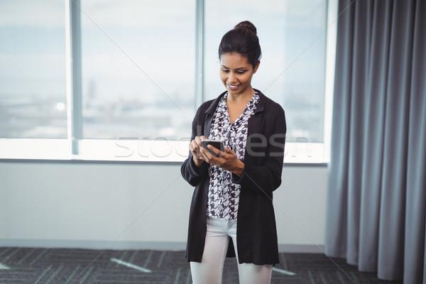 Vrouwelijke uitvoerende mobiele telefoon glimlachend kantoor internet Stockfoto © wavebreak_media
