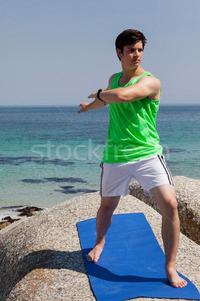 Hombre realizar yoga rock costa cielo Foto stock © wavebreak_media