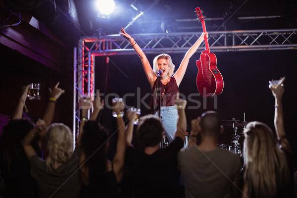 Női előadó karok a magasban énekel zene esemény Stock fotó © wavebreak_media