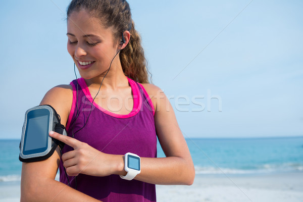 Smiling young woman touching arm band at beach Stock photo © wavebreak_media