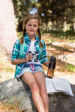 Girl with water bottle and binoculars sitting on the rock in forest Stock photo © wavebreak_media