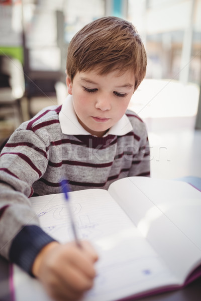 Attentive schoolboy writing in book in classroom Stock photo © wavebreak_media