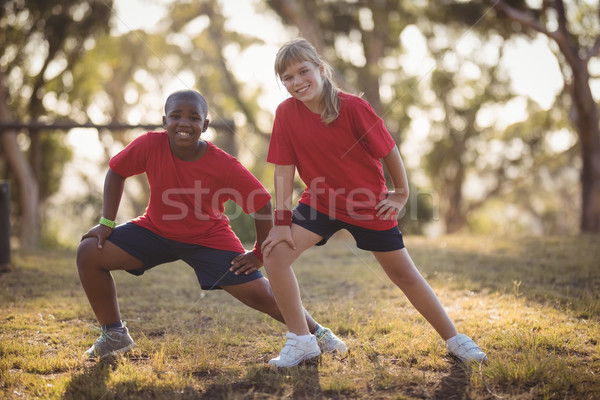 Portrait of happy kids performing stretching exercise during obstacle course Stock photo © wavebreak_media