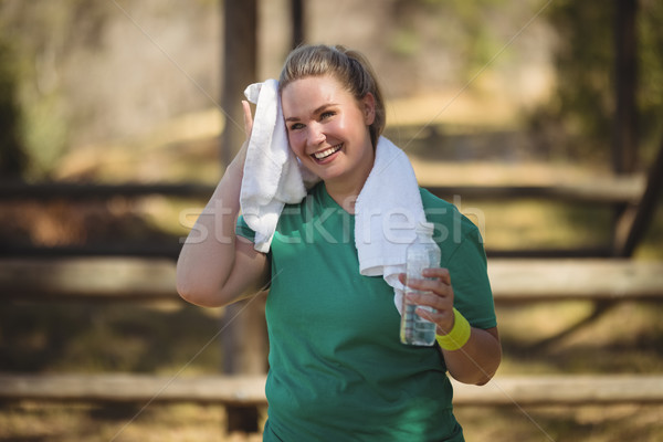 Happy woman wiping sweat with towel after workout Stock photo © wavebreak_media