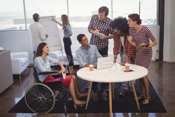 Business people discussing strategies with disabled colleagues in creative office Stock photo © wavebreak_media