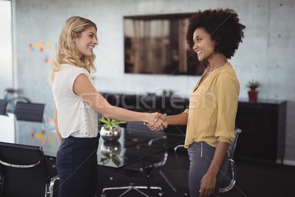üzletasszonyok kézfogás tárgyalóterem kreatív iroda mosolyog Stock fotó © wavebreak_media