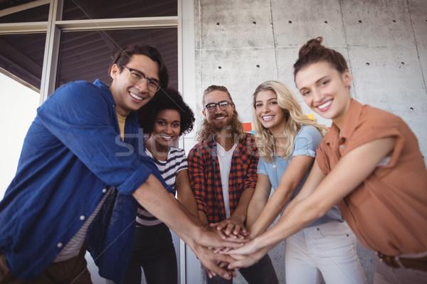 Creative business team stacking hands in office Stock photo © wavebreak_media
