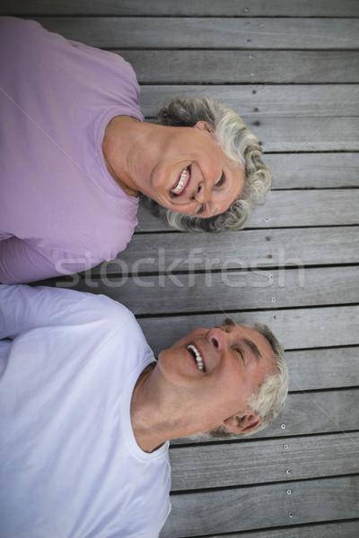 Overhead view of happy senior couple lying on wooden floor Stock photo © wavebreak_media