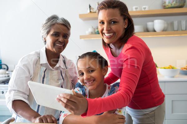 Multi-generation family using digital tablet in the kitchen Stock photo © wavebreak_media