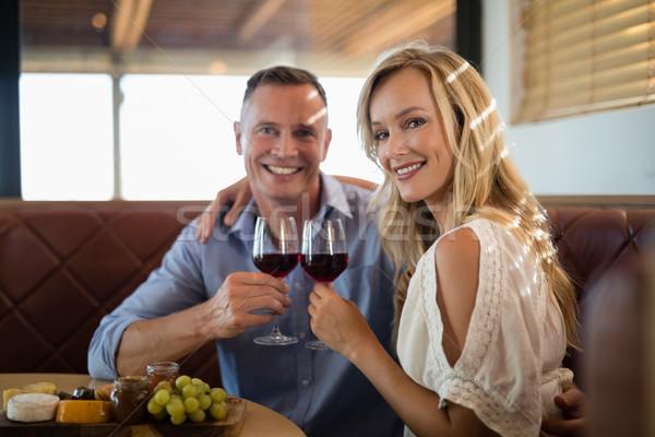 Happy couple holding wine glass while having meal Stock photo © wavebreak_media